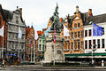 Bruges market suare belgium tourists walking and resting in restaurants abd cafes round the statue of jan breydel and pieter de Stock Images