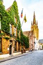 One of the many cobblestone streets in the heart of Bruges, Belgium with the tower of the Church of Our Lady in the backgound Royalty Free Stock Photo