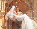 Bruidegom dragende bruid dichtbij kerk