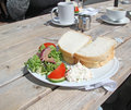 Brunch this photo shows a delicious pub lunch sandwiches and side salad on a white plate and set on a wooden table perfect Royalty Free Stock Photography