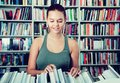 Brunete girl chooses a book in university library Royalty Free Stock Photo