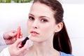 Woman applying lipstick on lips natural beauty