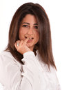Brunette biting her finger portrait of a in a white shirt against a neutral background Royalty Free Stock Photography