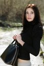 Brunette in black blouse pretty with big bag posing outdoors Stock Photography
