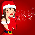 Brunette blowing christmas magic illustration of beautiful young in santa claus dress over red background Stock Photo