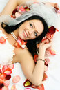 Brunette bride on the bed covered with rose leaves Stock Photo