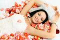 Brunette bride on the bed covered with rose leaves Royalty Free Stock Photo
