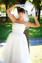 Brunette bride in the park a holding a white hat cylinder Stock Photo