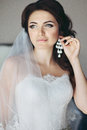 brunette bride in white dress putting on earring Royalty Free Stock Photo