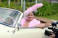 Brunette caliente en plumas rosadas en coche retro Foto de archivo