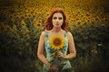 Brunette caucasian woman in blue dress at the park in flowers on a summer sunset holding sunflowers