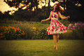 brunette caucasian woman in white and red dress at the park in red and yellow flowers on a summer sunset dancing in the meadow. C Royalty Free Stock Photo