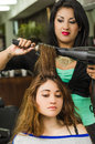 Brunette facing camera getting hair done by Royalty Free Stock Photo