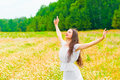 Brunette with a flower field with arms outstretched to the sides Stock Photo