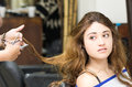 Brunette getting hair done by stylist hands while Royalty Free Stock Photo