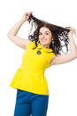 Brunette girl with curly hair wearing yellow blouse and blue pan beautiful pants over white background Royalty Free Stock Photo