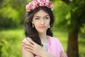 Brunette girl with flower chaplet in green filed wearing in pink Royalty Free Stock Photo