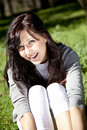 Brunette girl on green grass in the park. Royalty Free Stock Image