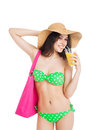 Brunette girl in green swimsuit and hat holding glass of orange beautiful pink bag juice over white background Stock Photography