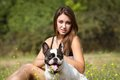 Brunette girl with her doggy teenage playing healthy young bulldog in the park Royalty Free Stock Photo
