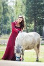 Brunette girl and horse young beautiful in long red dress play with white pony in green field Stock Photo