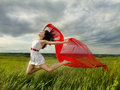 Brunette girl jumping with red fabric Royalty Free Stock Images