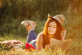 Brunette girl with long hair wearing dress and hat at picnic in sunny summer day.Attractive brunette woman lying among grass in me Royalty Free Stock Photo