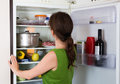 Brunette girl looking in fridge Royalty Free Stock Photo