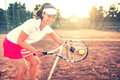 Brunette girl playing tennis with racket, balls and sports equipment. Close up portrait of beautiful woman on tennis cou Royalty Free Stock Photo