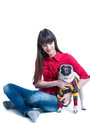 Brunette girl with a pug dog in a sweater pretty young wearing jeans and pink blouse sitting on the floor playing and holding her Royalty Free Stock Images