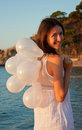 Brunette girl with white balloons on sunny beach Royalty Free Stock Photos