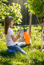 Brunette girl working in garden with fertilizing spray Royalty Free Stock Photo