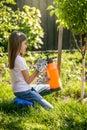 Brunette girl working in garden with fertilizing spray Royalty Free Stock Photo