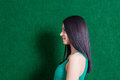 Brunette in green dress against wall profile shot of the cute black haired lady weared smiling Royalty Free Stock Photography