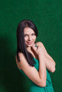 Brunette in green dress against wall weared smiling Stock Images