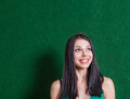 Brunette in green dress against wall weared smiling and looking up Royalty Free Stock Images