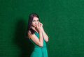 Brunette in green dress against wall weared standing torso shot Stock Photos
