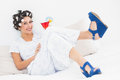 Brunette in hair curlers and wedge shoes holding a cocktail bedroom at home Stock Photo