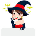 Brunette halloween witch beautiful woman with black and red costume smiling holding an empty billboard Royalty Free Stock Photos