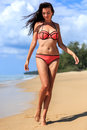 Brunette happy girl walking in the beach shore Royalty Free Stock Photo