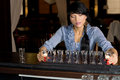 Brunette hostess aligning shot glasses on the bar attractive in a fancy location Royalty Free Stock Images