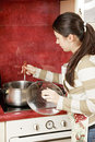 Brunette housewife stiring soup Royalty Free Stock Photo