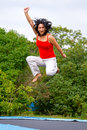 Brunette jumping on garden trampoline Royalty Free Stock Image