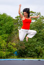 Brunette jumping on trampoline Stock Image
