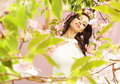 Brunette lady among the greenery and pink flowers Royalty Free Stock Photo