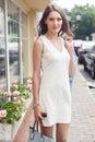 Brunette lady in white elegant dress on street background Royalty Free Stock Photo