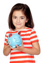 Brunette little girl with a blue moneybox Royalty Free Stock Photo