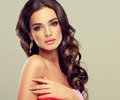 Brunette with long curled hair beautiful model in coral dress Royalty Free Stock Image