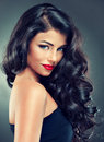 Brunette with long dense curly hair portrait model and bright lipstick tender smile Stock Photography