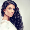Brunette with long dense curly hair portrait model in a white gown sincere kind look Stock Photography
